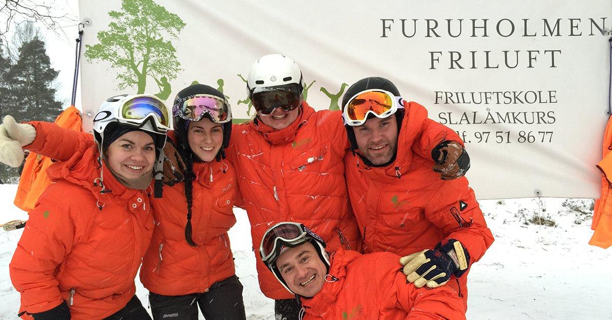 Fem skiinstruktører smiler til kameraet