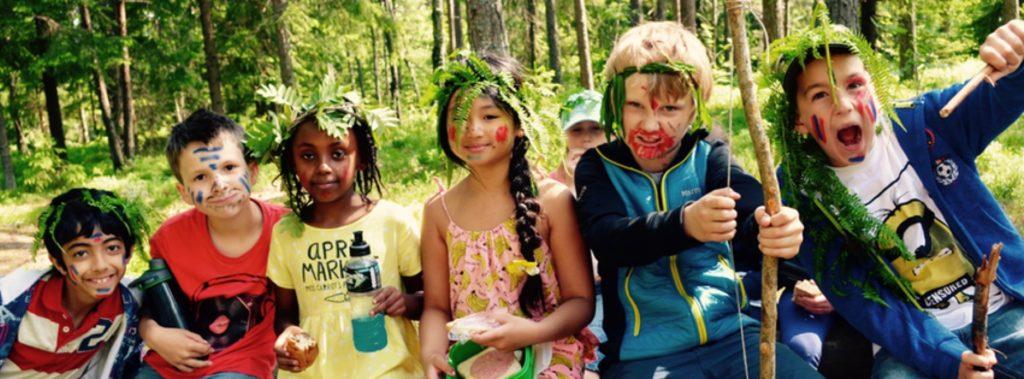 Bursdag.Fem barn leker ute i skogen.