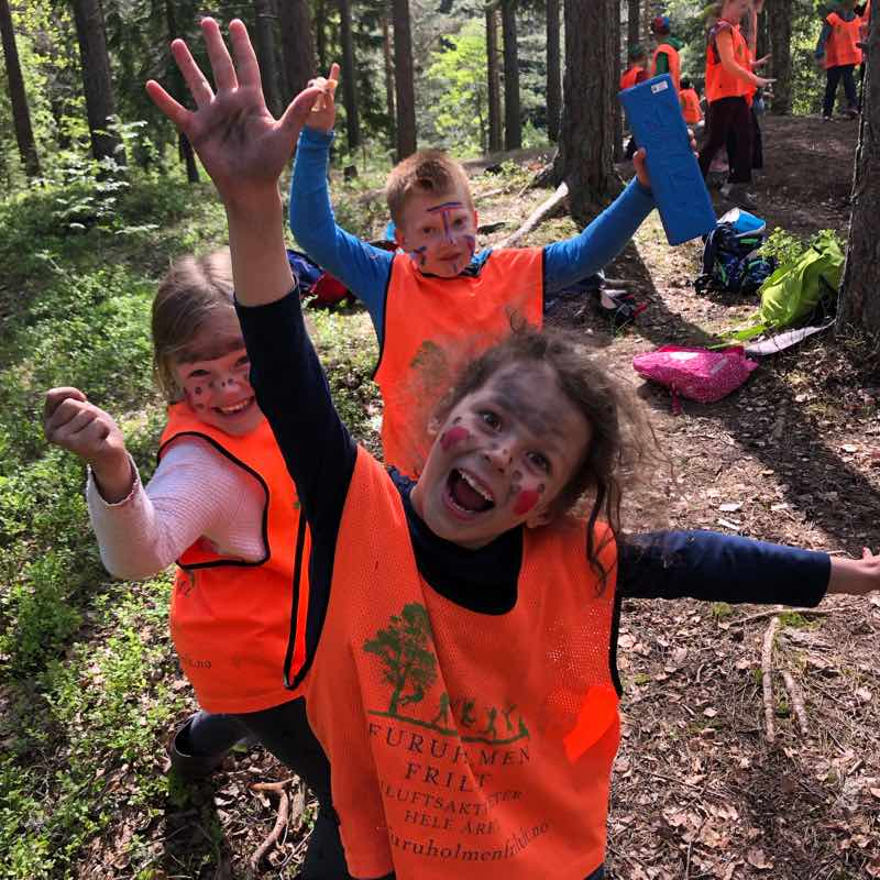 Tre glade barn med orange vest på Furuholmen Frilufts friluftsskole.