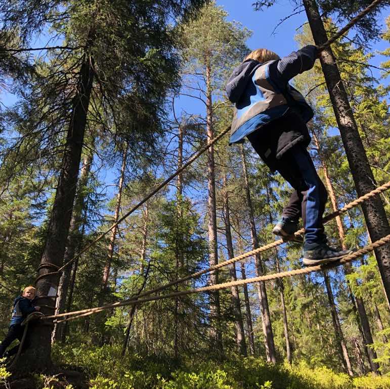 To barn i blå vester som balanserer på en taubro hos Furuholmen Friluft Friluftsskole