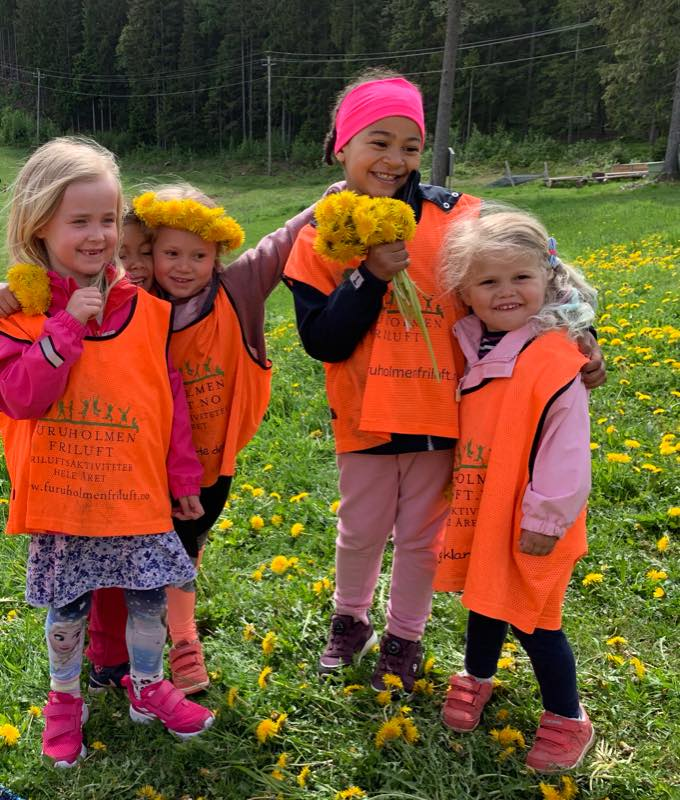 Fem glade jenter med blomsterkrans på utebursdag hos Furuholmen Friluft