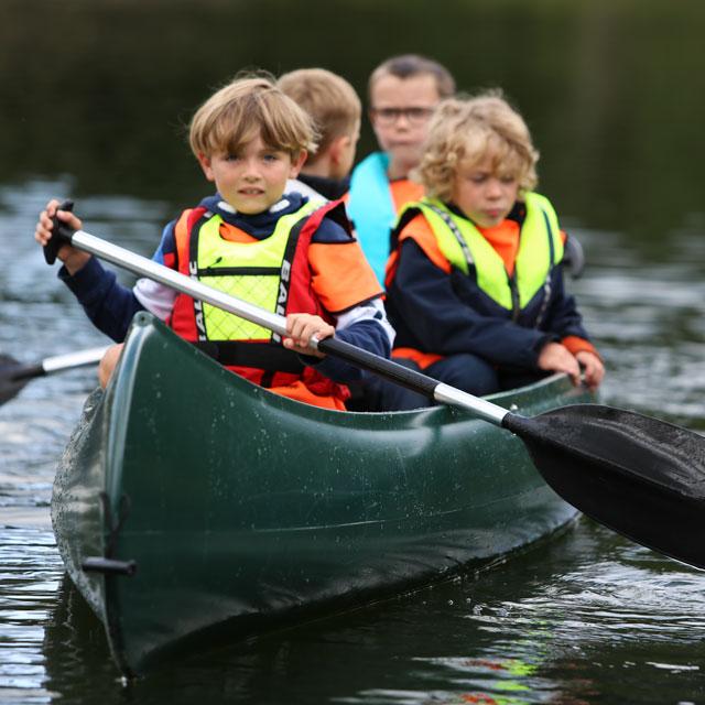 4 barn paddler i kano på Trollvann Grefsen