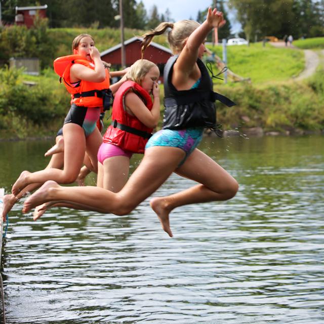 4 barn hopper i vannet fra brygge