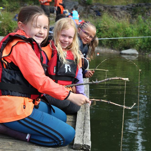 Tre jenter fisker med hjemmelagde fiskestenger i Trollvann på Grefsen